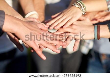 friendship, togetherness, team and people concept - close up of students or teenagers with hands outdoors