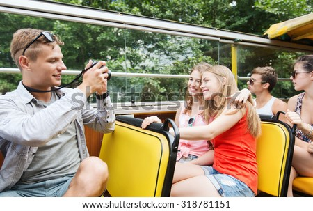 friendship, travel, vacation, summer and people concept - group of happy friends with digital camera traveling by tour bus and photographing