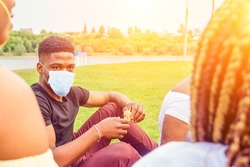 friendship young millennial multi-ethnic afro braids dreadlocks friends in medical mask talking spending weekend together autumn cloudy evening