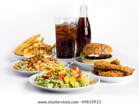 fries, hamburgers, chicken wings, salad with crab meat and cola on white background
