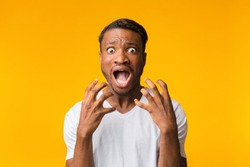 Fright. Terrified Afro Man Shouting Holding Hands Near Face Looking At Camera Standing Over Yellow Background. Studio Shot