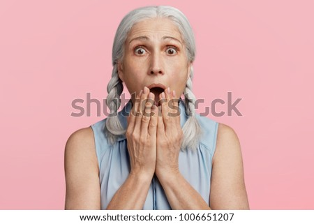 Frightened amazed grey haired female covers mouth, being shocked to hear bad news, expresses great surprsiment, scared of something, isolated over pink background. People and reaction concept #1006651207