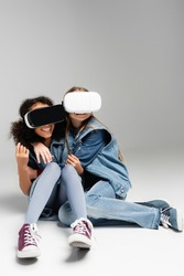 frightened and thrilled multicultural kids in vr headsets embracing while sitting on grey