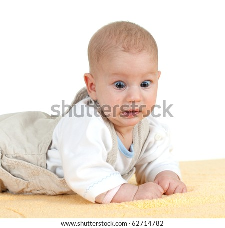 frightened baby boy on the yellow blanket