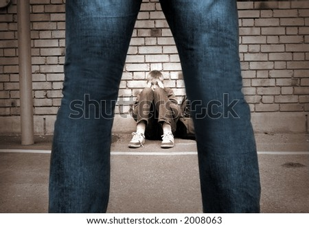 frightened boy at the school yard and a mans legs