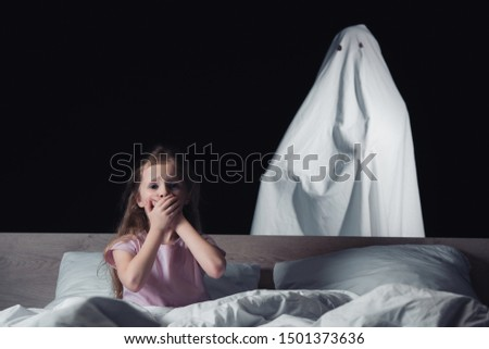 frightened child sitting in bed and showing hush sign while white ghost standing behind bed isolated on black  Сток-фото ©