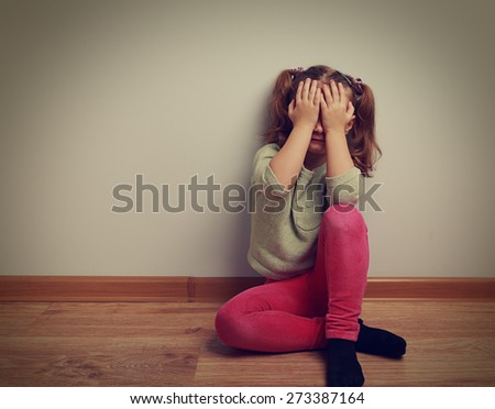 Frightened crying kid girl sitting on the floor with closed face the hands. Vintage closeup portrait