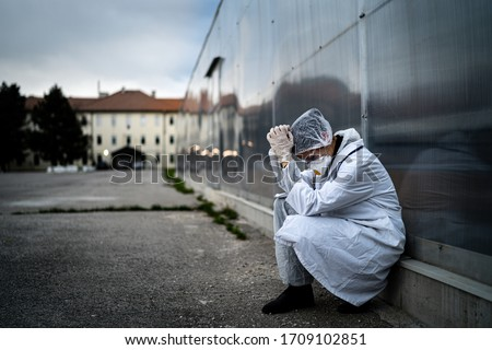 Frightened doctor for infectious diseases having mental nervous break down.Coronavirus COVID-19 exhausted physician in fear.Working in improvised medical facility isolation ward.Medical worker stress