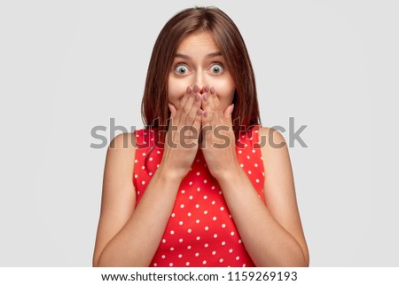 Frightened European female with bugged eyes, closes mouth with fright, being very emotional, afraids of something terrible, wears fashionable dress, isolated over white background. Emotions concept #1159269193