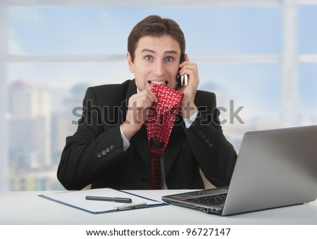 frightened frustrated business man talking on the phone, bites a tie, experiences fear and stress