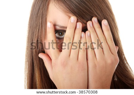 Frightened girl hiding her face behind her hands isolated on white background
