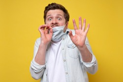 Frightened man in protective hygienic mask afraiding of coronavirus epidemic, infection, respiratory diseases such as flu, 2019-nCoV, ebola. Studio shot on yellow wall.