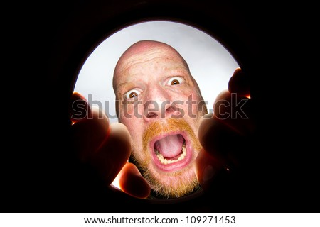 frightened man looking in a hole