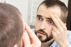 Frightened man sees wrinkles on his face, a man looks at himself in the bathroom mirror, portrait, close-up