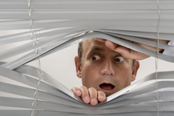 Frightened person looking through window shutter