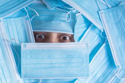 Frightened woman face covered with a bunch of disposable surgical masks with ear loops and pleats. Her beautiful eyes are wide open, full of delicate blood vessels.