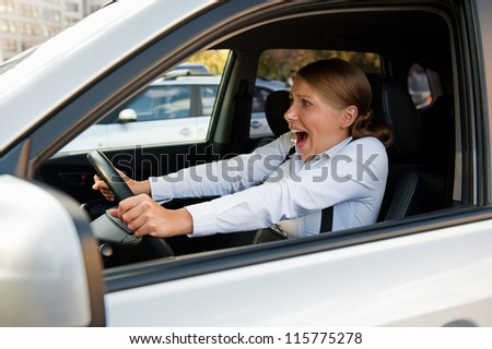 frightened woman sitting in the car and holding for the wheel
