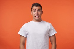 Frightened young brown-eyed brunette man with short haircut rounding amazedly his eyes while looking scaredly at camera, standing over orange background