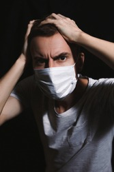 Frightened young guy in a medical mask. Young man in a protective mask against viruses panicky clutching his head