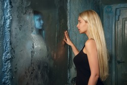 Frightened young woman looking in the mirror and seeing in reflection a ghost girl