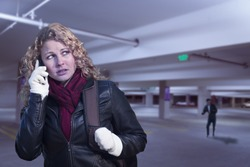 Frightened Young Woman On Cell Phone As Dark Man Lurks in Parking Structure.