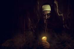 Frightening devilish possessed nun standing with a candle in a dark room. Horrors and Halloween.