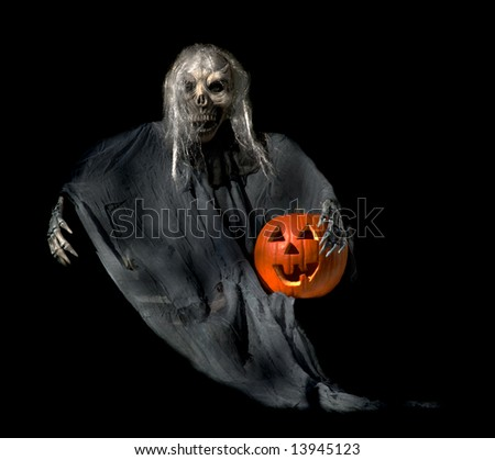 Frightening Halloween ghoul with a jack-o-lantern in his arm.