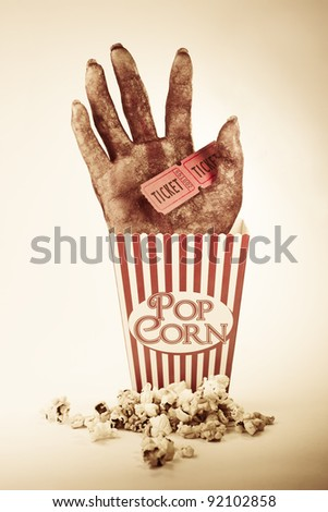 Frightening Picture Of A Creepy Sawn Off Hand Poking Out Of A Striped Pop Corn Box Holding Two Cinema Movie Tickets In A Horror Movie Conceptual