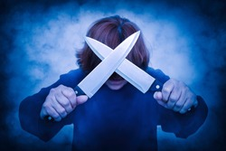 Frightening woman with hair covering her face holding two crisscrossed knives. Smoke effect applied. Halloween and horror concept.