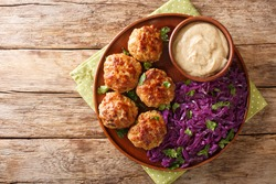 Frikadeller or Danish Meatballs are savory meatballs served with rich creamy sauce and stew red cabbage close up in the plate on the table. horizontal top view from above