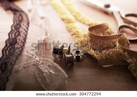 Fringe or lace tapes and silk trimmings with gold (brass) scissors and old sewing machine bobbins on a old grungy work table. Tailor's work table. textile or fine cloth making.Shallow depth of field. #304772294