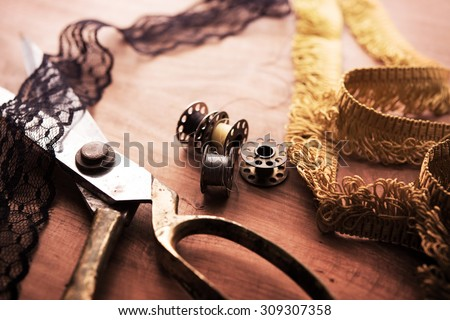 Fringe or lace tapes and silk trimmings with gold (brass) scissors and old sewing machine bobbins on a old grungy work table. Tailor\'s workbench. textile or fine cloth making.Shallow depth of field.