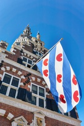 Frisian flag on the old renaissance style town hall in Franeker Friesland The Netherlands under a blue sky. Vertical image with copy space.
