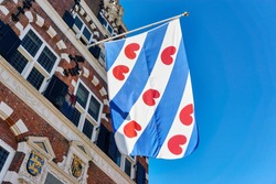 Frisian flag on the old renaissance style town hall in Franeker Friesland The Netherlands under a blue sky with copy space.