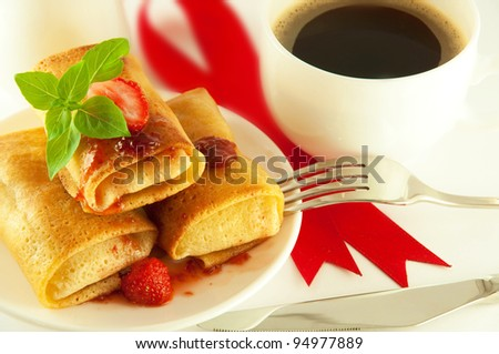 Fritters with red ribbon and mint and a cup of coffee
