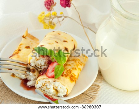 Fritters with strawberry jam and mint and a jug with milk