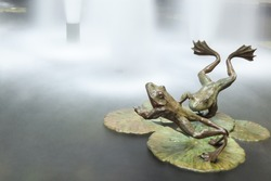 Frogs jump into water. Metal jumping frogs sculpture. Long exposure.