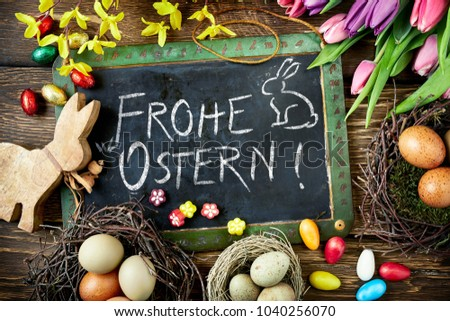 Frohe Ostern Easter greeting handwritten on a vintage school slate surrounded with cute wooden bunny cutout, eggs and fresh spring flowers viewed from above Stock foto ©