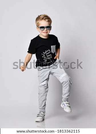 Frolic blond kid boy in sunglasses, black t-shirt with dinosaur print and gray pants stands with his foot up stamping loudly over gray background
