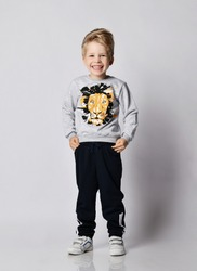 Frolic cheerful blond kid boy in black pants and sweatshirt with lion print giggles holding hands in pockets over gray background