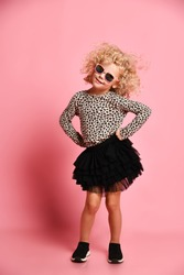 Frolic kid girl with curly blonde hair in sunglasses, modern fashion black skirt, leopard print sweatshirt and sneakers dances with her hands on her hips over pink background
