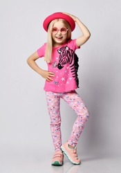 Frolic laughing blonde kid girl in round sunglasses, pink hat, t-shirt with zebra, butterflies, hearts and stars print holding hand on her head, the other on waist and knee up