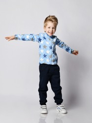 Frolic playful blond kid boy in blue pants, fleece jacket sweater with stars print pattern and white sneakers stands with arms spread wide whirling over gray background