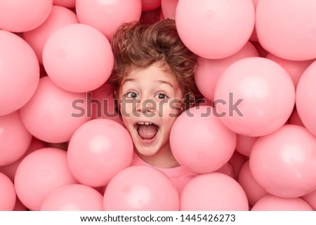 From above adorable boy with curly hair screaming and having fun while playing in heap of pink balloons #1445426273