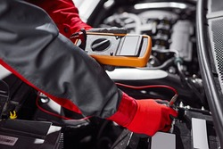 From above anonymous male mechanic using tester during diagnostic of vehicle battery during work in garage