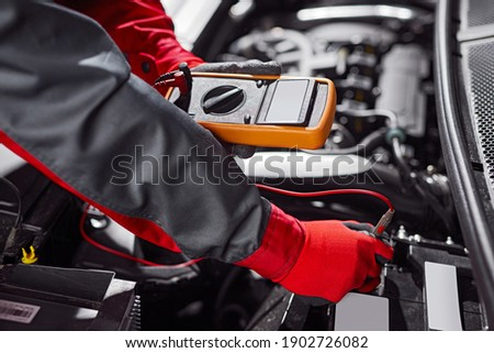 From above anonymous male mechanic using tester during diagnostic of vehicle battery during work in garage ストックフォト ©