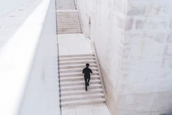 From above back view of man in black clothes with black hair going up white stairs near walls in city