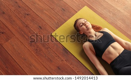 From above calm fit woman relaxing and breathing while lying at corpse pose on mat Foto stock ©