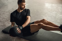 From above determined sportsman doing abs exercise with ball on mat during fitness training in gym