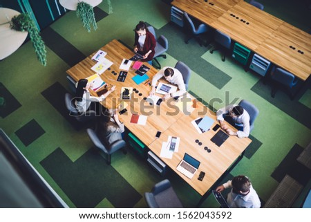 From above executives in formal wear sitting at meeting table with documents and laptop having conversation discussing work plan in company  #1562043592